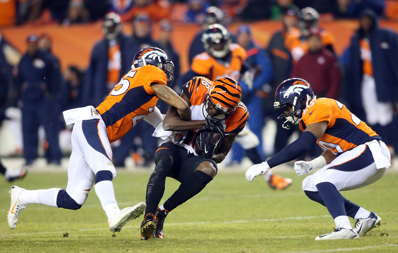 Cincinnati Bengals wide receiver A.J. Green (18) is brought down by Denver Broncos cornerback Chris Harris (25) and defensive back Josh Bush (20) during the first half at Sports Authority Field at Mile High on Dec. 28, 2015. Photo courtesy of Chris Humphreys-USA TODAY Sports via Reuters.  *Editors: This photo may only be republished with RNS-CAMOSY-COLUMN, originally transmitted on Dec. 30, 2015.