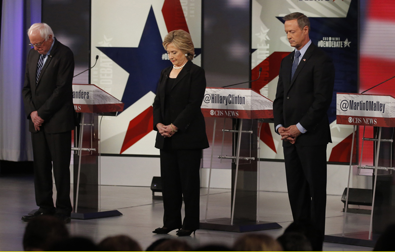 Democratic U.S. presidential candidates Senator Bernie Sanders (L), former Secretary of State Hillary Clinton and former Maryland Governor Martin O'Malley bow their heads in a moment of silence for the recent attacks in Paris ahead of the second official 2016 U.S. Democratic presidential candidates debate in Des Moines, Iowa, on November 14, 2015. Phtoo courtesy of REUTERS/Jim Young