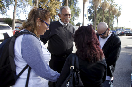 Chaplain Rob Reyes, second left, prays with relatives of a worker who was not injured, but expected at the Rudy Hernandez Community Center, after a shooting incident at the Inland Regional Center in San Bernardino, California on December 2, 2015. Photo courtesy of REUTERS/Alex Gallardo *Editors: This photo may only be republished with RNS-MERRITT-COLUMN, originally transmitted on Dec. 3, 2015.