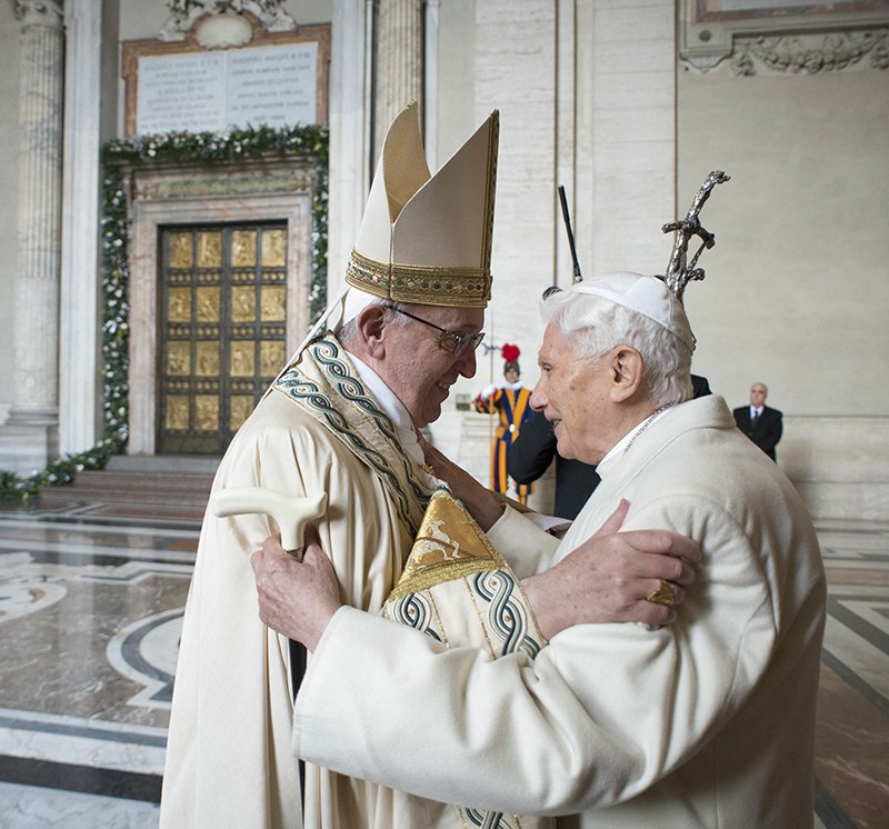 Pope Francis embraces Emeritus Pope Benedict XVI before opening the Holy Door to mark opening of the Catholic Holy Year, or Jubilee, in St. Peter's Basilica, at the Vatican, on December 8, 2015. Photo courtesy of REUTERS/Osservatore Romano/Handout via Reuters *Editors: This photo may only be republished with RNS-POPE-HOLYYEAR, originally transmitted on Dec. 8, 2015.