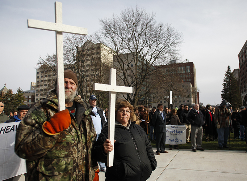Steven Freund and wife Lori of God's House Mission in Gladwin wield crosses on December 2, 2015, at the State Capitol during a rally to protect religious liberty. Photo courtesy of USA Today
