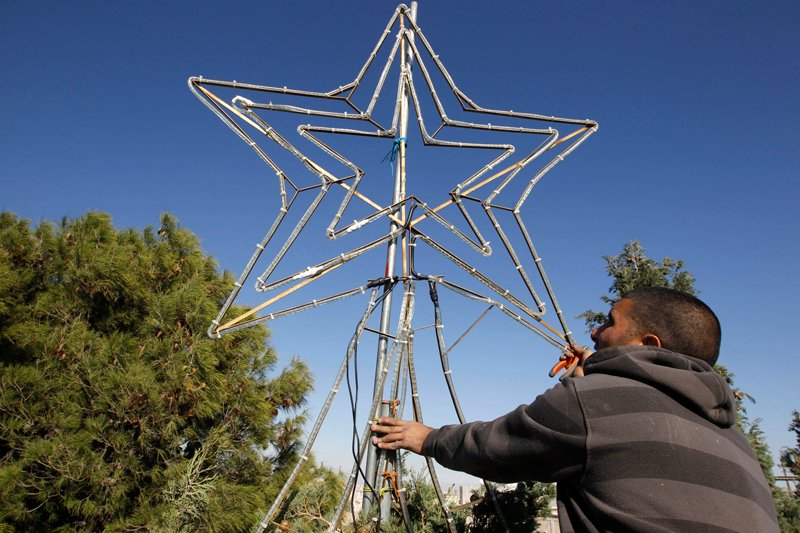 A Palestinian municipality worker places a star on top of a tree before the annual lighting ceremony of a Christmas tree at Manger Square in the West Bank town of Bethlehem on December 15, 2010. Photo courtesy of REUTERS/Ammar Awad *Editors: This photo may only be republished with RNS-STAR-SPLAINER, originally transmitted on Dec. 21, 2015.