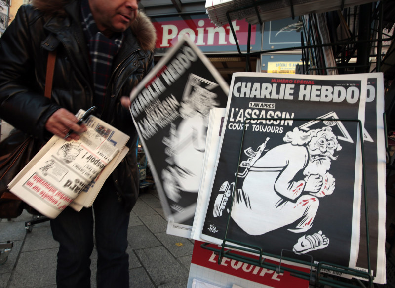 "A man takes a copy of the latest edition of French weekly newspaper Charlie Hebdo with the title ""One year on, The assassin still on the run"" displayed at a kiosk in Nice, France, January 6, 2016. France this week commemorates the victims of last year's Islamist militant attacks on satirical weekly Charlie Hebdo and a Jewish supermarket with eulogies, memorial plaques and another cartoon lampooning religion. Photo by Eric Gaillard, courtesy of Reuters."