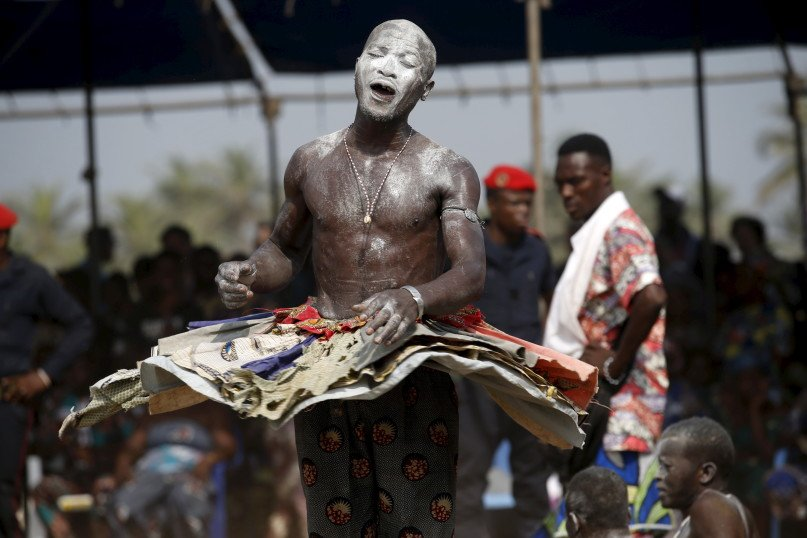A devotee dances at the annual voodoo festival in Ouidah January 10, 2016. The national voodoo holiday in the West African country of Benin had a distinctively political accent this year as practitioners from Africa and the Americas gathered on Sunday to offer prayers and sacrifices for peace. REUTERS/Akintunde Akinleye.