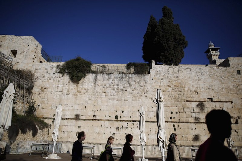 Tourists walk by part of the Western Wall, following the Israeli government's approval to create a mixed-sex prayer plaza near Jerusalem's Western Wall to accommodate Jews who contest Orthodox curbs on worship by women at the site, in Jerusalem's Old City January 31, 2016. Photo courtesy REUTERS/Amir Cohen