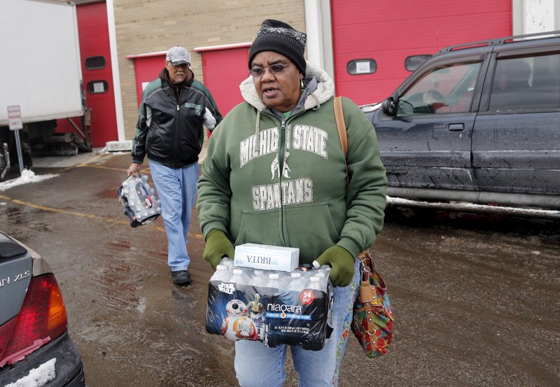Flint resident Ruby Adolph carries bottled water and a replacement water filter she received at a fire station in Flint, Michigan on January 13, 2016. Photo courtesy of REUTERS/Rebecca Cook *Editors: This photo may only be republished with RNS-FLINT-FAITH, originally transmitted on Jan. 19, 2016.