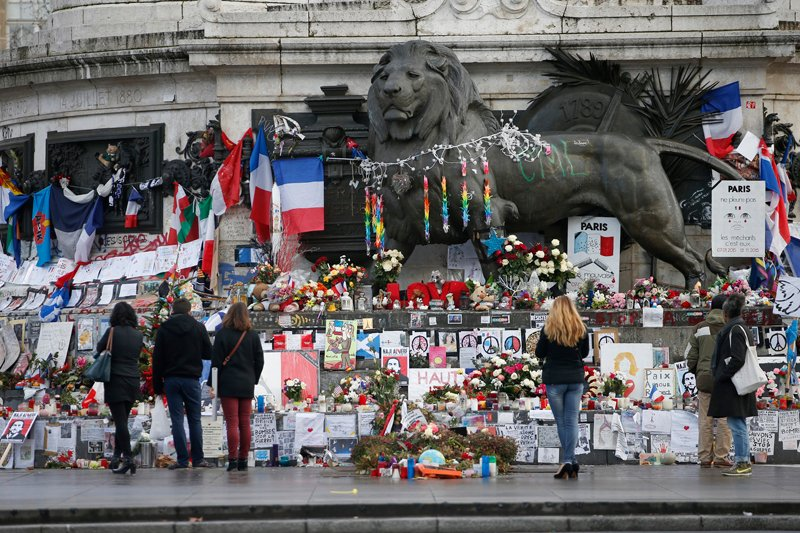 People look at flowers and messages to pay tribute to the victims of last year's January and November shooting attacks near the statue at the Place de la Republique in Paris, France, on January 6, 2016. France this week commemorates the victims of last year's Islamist militant attacks on satirical weekly Charlie Hebdo and a Jewish supermarket with eulogies, memorial plaques and another cartoon lampooning religion. Photo courtesy of REUTERS/Charles Platiau *Editors: This photo may only be republished with RNS-FRANCE-ANTISEMITISM, originally transmitted on Jan. 6, 2016.