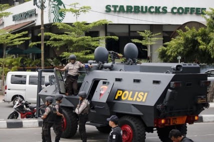 Indonesian policemen stand guard in front of a Starbucks in Jakarta, January 14, 2016. Militants launched a gun and bomb assault in the center of the Indonesian capital. Photo courtesy of Reuters.
