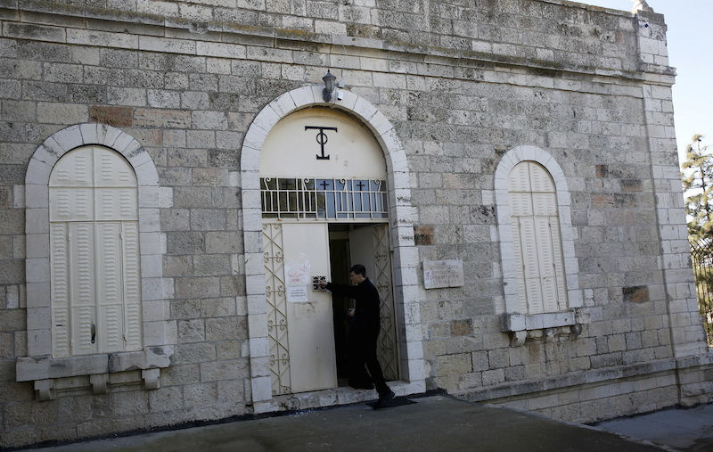 An Orthodox monk cleans graffiti from a door of the Greek Orthodox Seminary, located next to the Dormition Abbey on Mount Zion in Jerusalem's Old City January 17, 2016. REUTERS/Ronen Zvulun -
