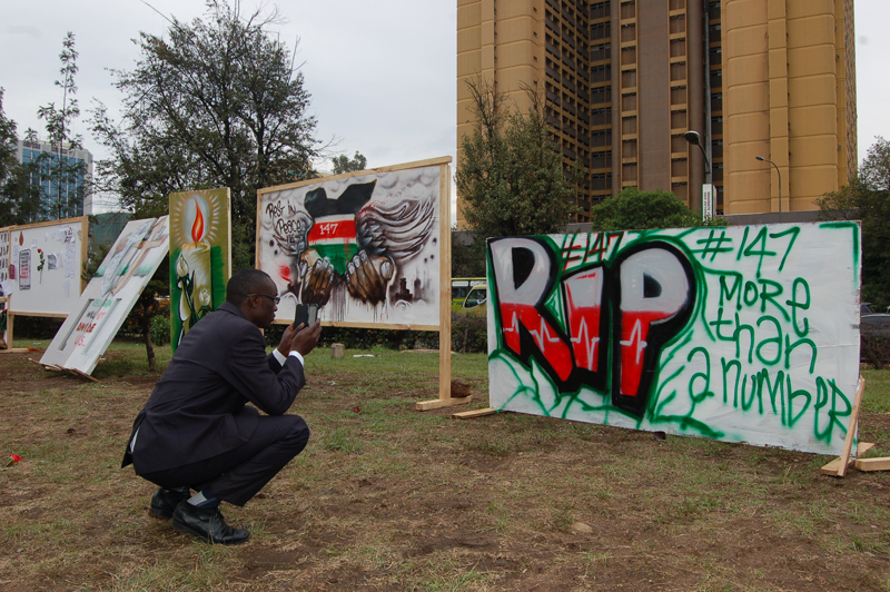 A man takes a photo of the art on display in Uhuru Park, mourning the deaths of Garissa University students. Religion News Service photo by Fredrick Nzwili