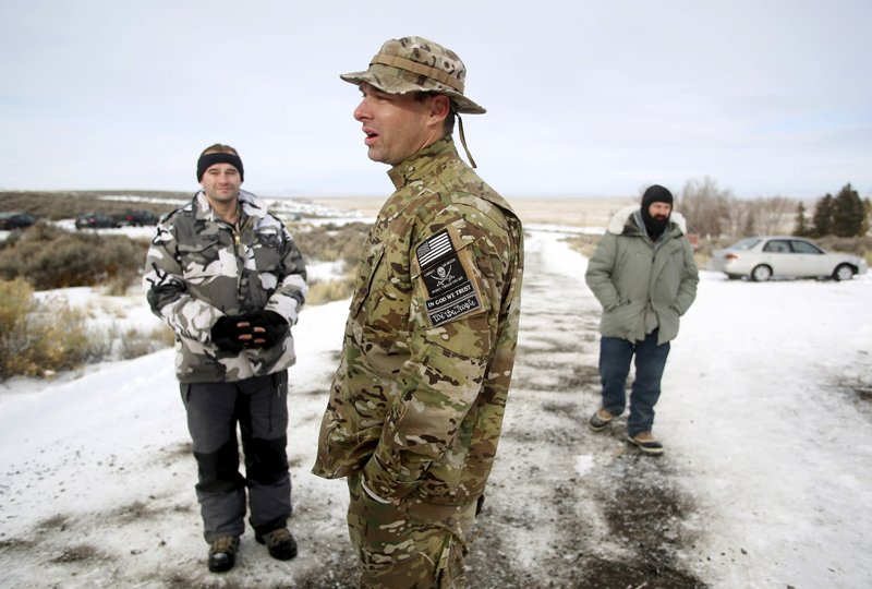 "Militiamen stand on a road at the Malheur National Wildlife Refuge near Burns, Ore., on January 4, 2016. The leaders of a group of self-styled militiamen who took over a U.S. wildlife refuge headquarters over the weekend said on Monday they had acted to protest the federal government's role in governing wild lands. Ammon Bundy, a leader of the group, told reporters outside the occupied facility on Monday that his group had named itself ""Citizens for Constitutional Freedom"" and was trying to restore individual rights. Bundy and law enforcement officials declined to say how many people were occupying the refuge headquarters. Photo courtesy of REUTERS/Jim Urquhart *Editors: This photo may only be republished with RNS-LDS-OREGON, originally transmitted on Jan. 5, 2016."