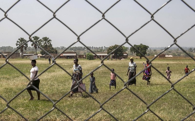Residents walk through a path as they arrive to watch a live pre-trial screening of former Lord's Resistance Army (LRA) commander Dominic Ongwen's case facilitated by the International Criminal Court (ICC), at Lukodi primary school in Gulu, north of Uganda's capital Kampala, on January 21, 2016. International prosecutors on Thursday accused Ongwen of using rape and brutality to turn children the LRA had abducted into sex slaves or soldiers for its long campaign against Uganda's government. Photo courtesy of REUTERS/Edward Echwalu *Editors: This photo may only be republished with RNS-LRA-CAR, originally transmitted on Jan. 27, 2016.