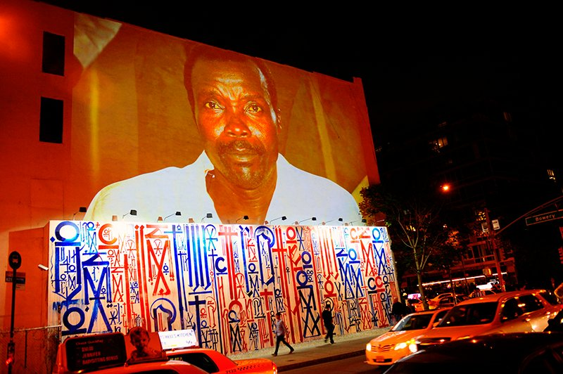 """Passersby walk under a projection that is part of the non-profit organization Invisible Children's """"Kony 2012"""" viral video campaign, in New York on April 20, 2012. Invisible Children shot to prominence in March 2012 when its video on Ugandan warlord Joseph Kony and his brutal Lord's Resistance Army drew more than 100 million hits on social media. Photo courtesy of REUTERS/Keith Bedford *Editors: This photo may only be republished with RNS-LRA-CAR, originally transmitted on Jan. 27, 2016."""