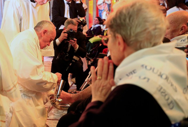 Pope Francis washes a foot of a disabled person at the S. Maria della Provvidenza church in Rome, during the Holy Thursday celebration, April 17, 2014. Pope Francis visited a rehabilitation centre at the church, on Rome's outskirts, for a service in which he washed and kissed the feet of 12 sick and disabled people. REUTERS/Tony Gentile (ITALY - Tags: RELIGION) - RTR3LPHM
