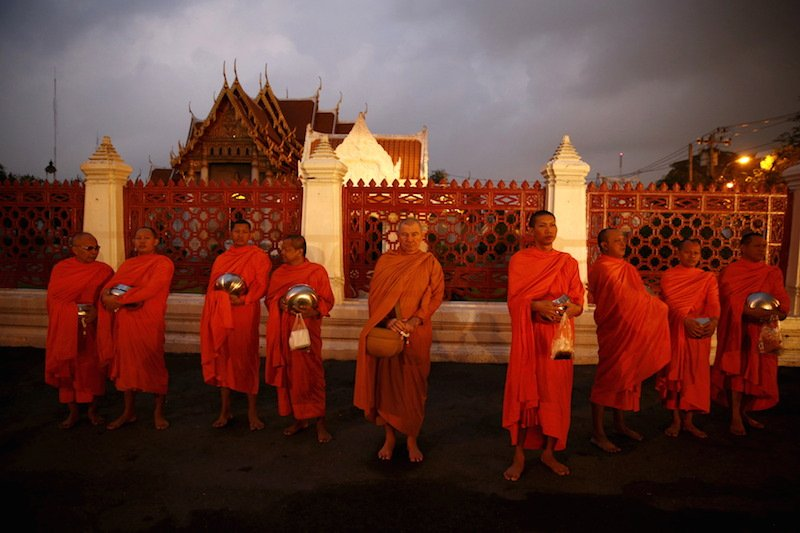 Buddhist monks line up outside a temple to receive food early morning in Bangkok, Thailand, January 14, 2016. Political divisions and allegations of corruption are fueling an unholy battle for the leadership of Thai Buddhism. REUTERS/Jorge Silva - RTX22AY6