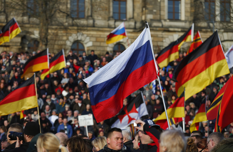 Supporters of the anti-Islam movement Patriotic Europeans Against the Islamisation of the West (PEGIDA) carry German and Russian flags during a demonstration in Dresden, Germany, February 6, 2016.  REUTERS/Hannibal Hanschke.
