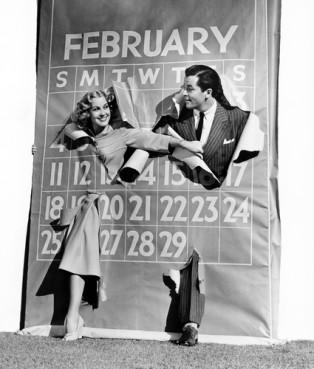 Couple bursting through leap year calendar.
