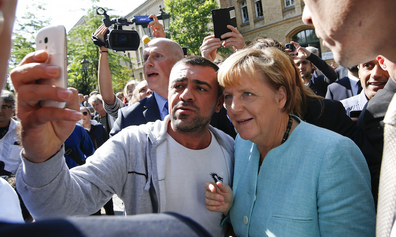 A migrant takes a selfie with German Chancellor Angela Merkel outside a refugee camp near the Federal Office for Migration and Refugees after registration at Berlin's Spandau district, Germany Sept. 10, 2015. Photo courtesy REUTERS/Fabrizio Bensch