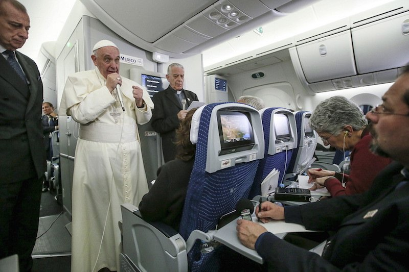 Pope Francis gestures during a meeting with the media onboard the papal plane while en route to Rome, Italy February 17, 2016. Picture taken February 17, 2016. Photo courtesy REUTERS/Alessandro Di Meo/Pool