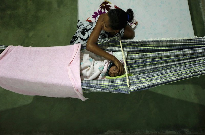 Miriam Araujo, 25, caresses Lucas, her 4-months old child born with microcephaly as he sleeps on a hammock inside their house, in Sao Jose dos Cordeiros, Brazil February 16, 2016. Photo courtesy REUTERS Ricardo Moraes *Editors: This photo may only be republished with RNS-BRAZIL-OB/GYN, transmitted on Feb. 26, 2016.