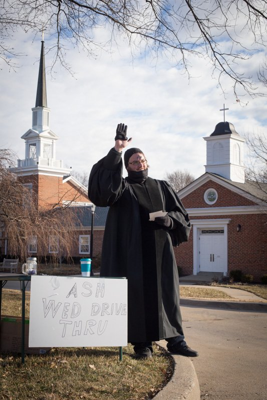 Ministerial intern Shea Zellweger, waves to passing cars along Mission Rd. in Prairie Village, Kan., on Feb. 10, 2016. For the fourth year, Colonial Church, United Church of Christ, is offering drive thru service on Ash Wednesday. Religion News Service photo by Sally Morrow