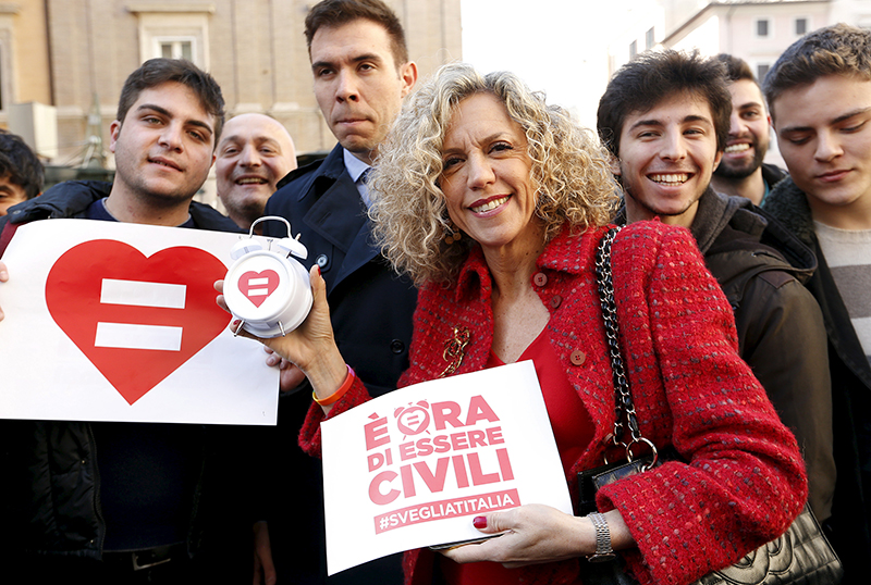 "Democratic Party Senator Monica Cirinna holds a placard as she poses with supporters of gay civil unions outside the Italian Senate in Rome, on January 28, 2016. Senate will begin debate on a bill that would legalise civil partnership for homosexuals as well as unmarried heterosexual couples. The placard reads: "" It's time to be civil"".  Photo courtesy of REUTERS/Remo Casilli *Editors: This photo may only be republished with RNS-ITALY-GAY, originally transmitted on Feb. 2, 2016."