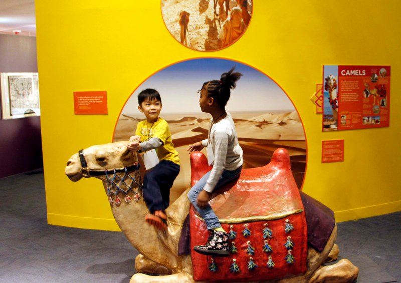"""Children enjoying a ride on a life-size camel in the Trade Routes area of the """"America to Zanzibar: Muslim Cultures Near and Far"""" exhibit at the Children's Museum of Manhattan. Photo courtesy of Aoommie Photography"""