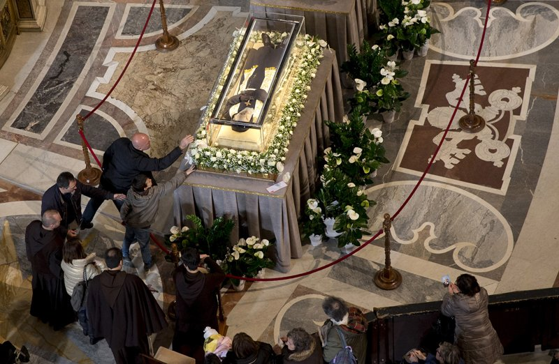 Faithful pray in front of the crystal coffins containing the exhumed bodies of the mystic saint Padre Pio displayed in Saint Peter's Basilica during a Jubilee day for the mystic saint Padre Pio at the Vatican on February 6, 2016. REUTERS/Alessandra Tarantino/Pool*Editors: This photo may only be republished with RNS-PADRE-PIO, originally transmitted on Feb. 11, 2016.