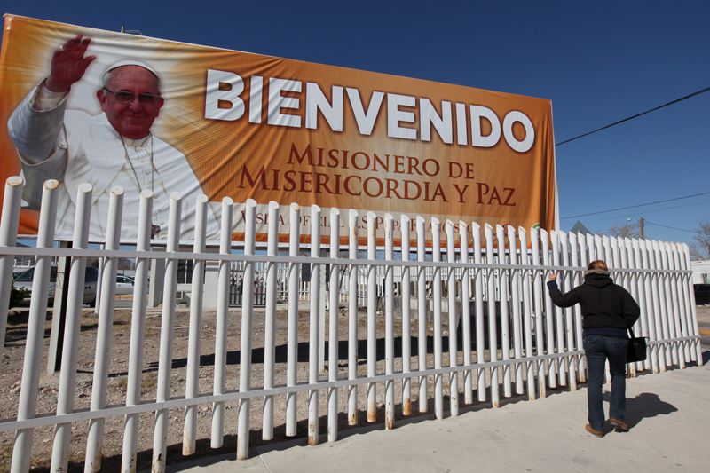 A woman gestures as she walks by a billboard promoting the upcoming visit of Pope Francis, outside the Cereso 3 prison in Ciudad Juarez, Mexico, on February 5, 2016. Photo courtesy of REUTERS/Jose Luis Gonzalez *Editors: This photo may only be republished with RNS-POPE-MEXICO, originally transmitted on Feb. 10, 2016.