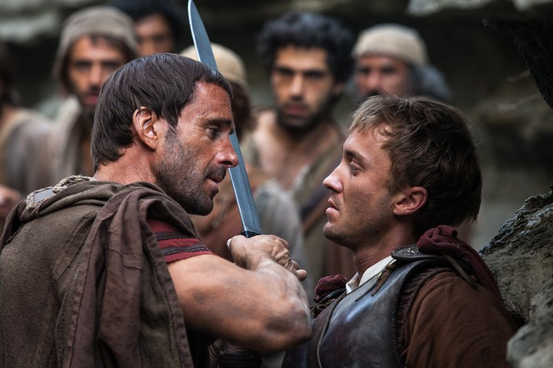 Clavius (Joseph Fiennes, left) warns Lucius (Tom Felton) to let them all pass, after he discovers him leading the apostles away from the Roman soldiers in Columbia Pictures' RISEN. Photo courtesy of Columbia Pictures