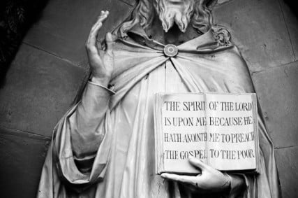 """A statue of Jesus holding the message, """"The spirit of the Lord is upon me because he hath anointed me to preach the gospel to the poor."""
