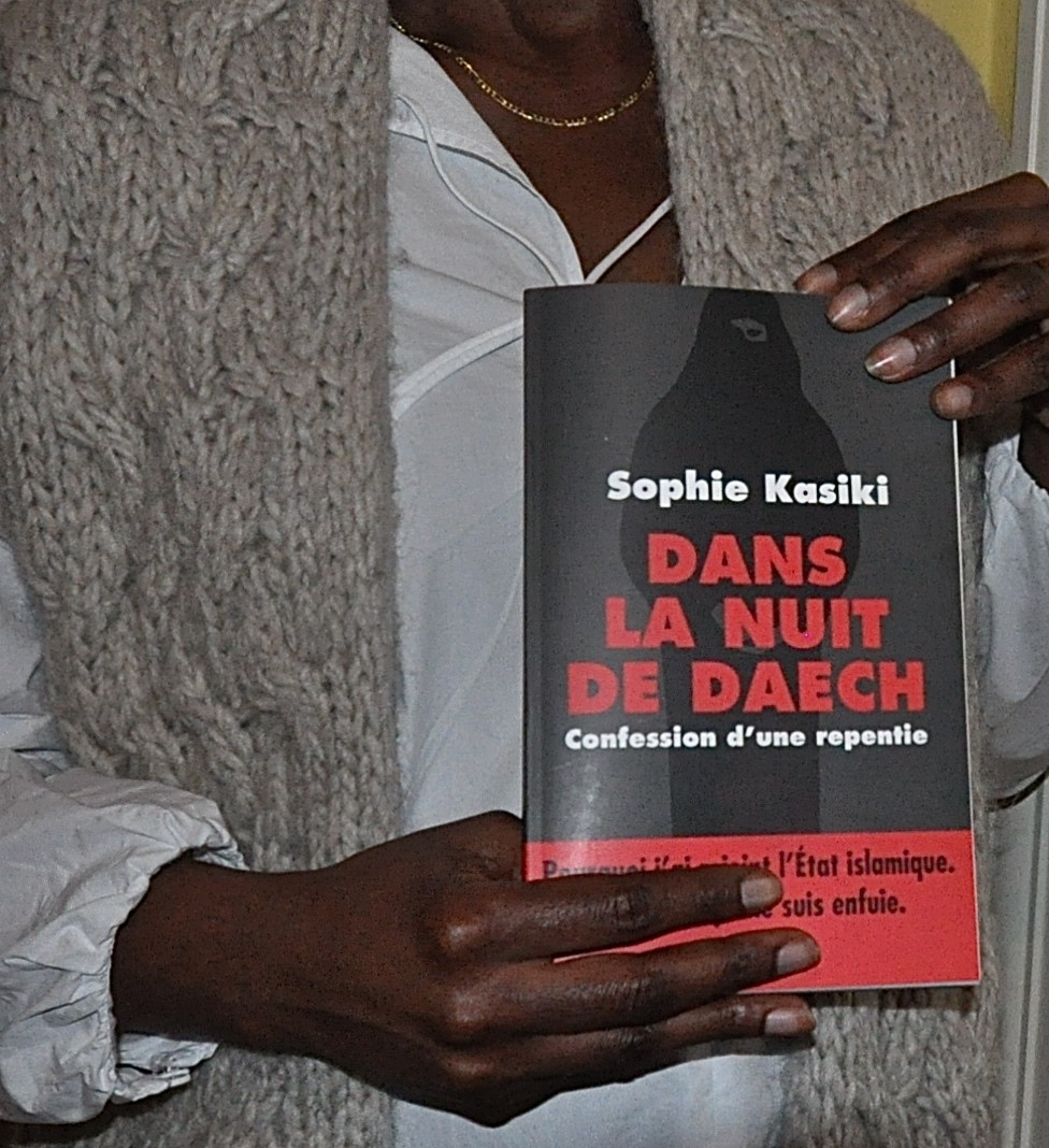 "Sophie Kasiki, one of the few Western women to have seen Islamic State's harsh ""caliphate"" in Syria and escaped, holds her book recently published in France that tells her story. The title Dans la Nuit de Daech (In the Night of Deash) uses the common French term for ISIS. The subtitle is ""Confession of a repentant"". Photo taken on March 17, 2016. Religion News Service photo by Tom Heneghan"