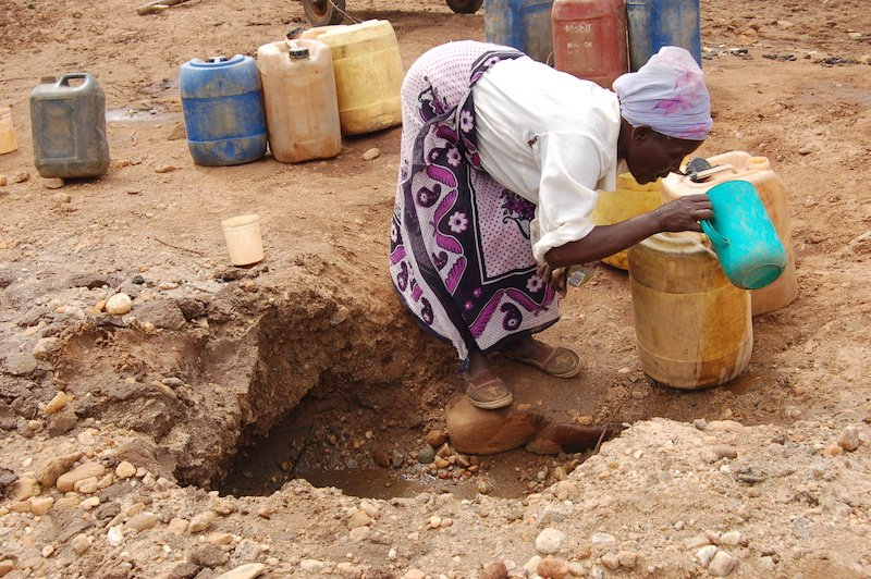 A woman scoops water from a dry river bed in Machakos in Eastern Kenya. The drought has worsened along the horn of Africa. Photo courtesy Fredrick Nzwili