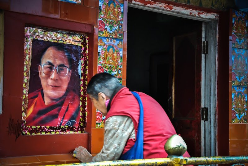 A Tibetan man bows down before the photo of the Dalai Lama at a prayer wheel in the north Indian town of Dharamsala, the seat of the spiritual leader of the Tibetan people. Photo courtesy Vishal Arora.