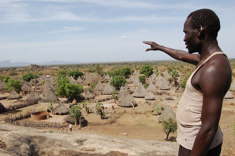 A man points at a village in rural South Sudan before the civil war. Most of the villages have been destroyed in the war. RNS photo courtesy Fredrick Nzwili