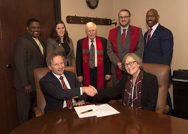 Left to right, back row, Gene Butler, Jill Goddard, Rev. Richard Gilbert, Rev. Aaron Stockwell, Lee Shaw, seated left to right, Michael Surbaugh, and Rev. Mary Katherine Morn, during the signing of an agreement between the Boy Scouts of America and the Unitarian Universalist Association on March 24, 2016, after the two organizations had previously been divided over gay rights. Photo courtesy of Photo by Boy Scouts of America