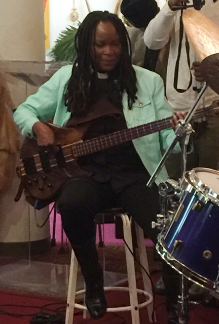 The Rev. Wanika Stephens plays the electric bass guitar during the Palm Sunday mass at St. John Coltrane Church while a standing-room-only crowd waved its greenery and bopped to the beat. Religion News Service photo by Kimberly Winston
