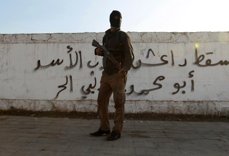 "A Free Syrian Army fighter carries his weapon as he stands in front of graffiti that reads ""Daesh (Islamic State of Iraq and the Levant ) down"" at Masaken Hanano neighborhood in Aleppo on January 7, 2014. Photo courtesy of REUTERS/Jalal Alhalabi *Editors: This photo may only be republished with RNS-ISIS-ESCAPE, originally transmitted on March 22, 2016."