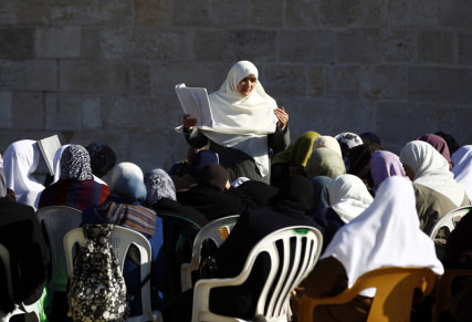 A Palestinian woman teaches from the Koran in front of al-Aqsa mosque on the compound known to Muslims as Noble Sanctuary and to Jews as Temple Mount in Jerusalem's Old City on November 28, 2012. Jerusalem's Old City is holy to the world's three major monotheistic religions, Judaism, Christianity and Islam. For Jews it incarnates ancient Israel, for Christians it is where Christ spent the last days of his life and for Muslims, it is where the Prophet Mohammad ascended to heaven. Photo courtesy of REUTERS/Marko Djurica *Editors: This photo may only be republished with RNS-ISRAEL-POLL, originally transmitted on March 8, 2016.