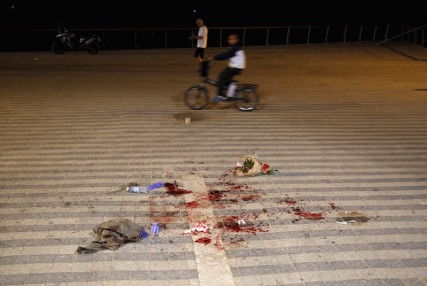 A boy rides past blood stains where, according to Israeli police spokesperson, at least 10 Israelis were stabbed, in the popular Jaffa port area of Tel Aviv, Israel on March 8, 2016. Photo courtesy of REUTERS/Amir Cohen