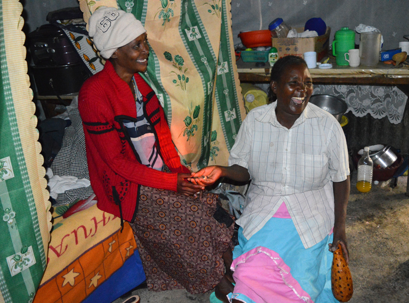 A traditional healer in Eastern Kenya shares a light moment with a patient in a 2014 photo. Healers like this one have joined with Christian leaders to help detect and refer mental illnesses to clinics in Makueni. Religion News Service photo by Fredrick Nzwili