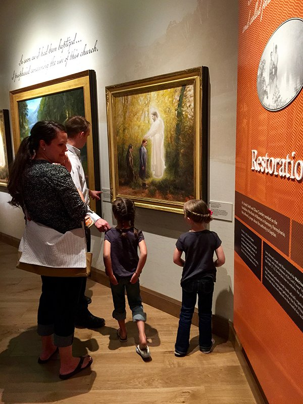 On a trip to the Church History Museum in Salt Lake City, Jason and Mysha Denson of Springville, Utah uses the framed art to teach her daughters Ella, 7, and Rivers, 5, about church doctrine and history. Religion News Service photo by Kimberly Winston