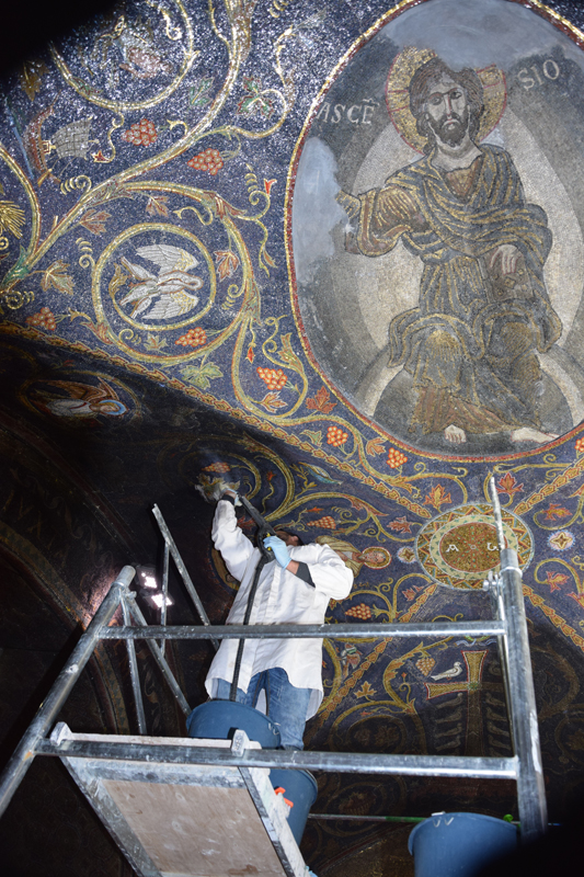 A Palestinian mosaic expert from the Mosaic Center, Jericho cleans and restores a part of the mosaic that adorns the ceiling of the Catholic section of the Calvary, or Golgotha, the room that marks the hill where Jesus was crucified. Photo courtesy of the Mosaic Center, Jericho