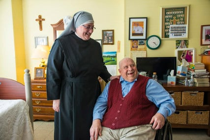 """Sister Constance Veit of Little Sisters of the Poor shares a laugh with resident Carl """"The Mayor"""" Bergquist, 78, on Monday, March 21, 2016 in Washington, D.C. The Little Sisters of the Poor filed a complaint against the Affordable Care Actís contraceptive mandate in 2013. """"The common misconception is that Form 700 is an opt out by which we sign off that we object to these services and then we are removed from any association with them. But in reality, it's an opt in or a permission slip by which, if we were to sign it, we would be granting the government authorization to enter into our healthcare plan, to take it over, said Veit,"""" from the point of view of respecting the sincerely held religious beliefs of others, it's troublesome to me. I don't really understand how they could be taking a position that this is a compelling interest in our case for our relatively small number of employees when one hundred million people are exempt. It just does't really make sense."""" Their case will be argued in the Supreme Court on Wednesday. Photo by Jarrad Henderson, courtesy of USA Today"""