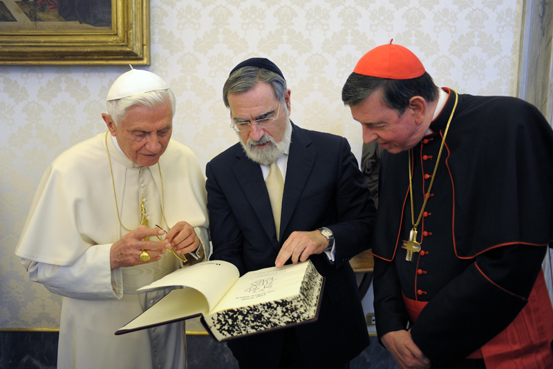 Pope Benedict XVI, left, receives a gift by Lord Jonathan Sacks, center, then chief rabbi of the United Hebrew Congregations of the Commonwealth, during a private audience at the Vatican on December 12, 2011. Photo courtesy of REUTERS/Osservatore Romano *Editors: This photo may only be republished with RNS-SACKS-TEMPLETON, originally transmitted on March 2, 2016.