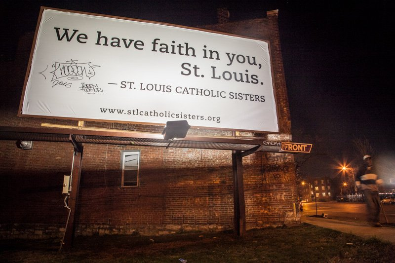 A St. Louis Catholic Sisters billboard is lit up at night in South City, St. Louis, Mo., on March 14, 2016. Religion News Service photo by Sally Morrow