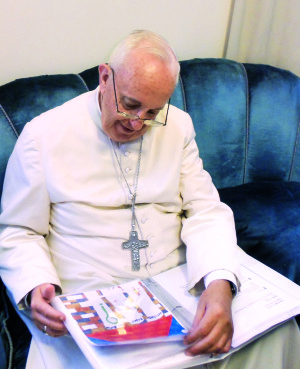 In his office in the Vatican, Pope Francis read the letters with questions submitted by children around the world. The letters, along with his answers, were published in a new book from Loyola Press, Dear Pope Francis: The Pope Answers Letters from Children Around the World. Photo by Antonio Spader, S.J., courtesy of Loyola Press