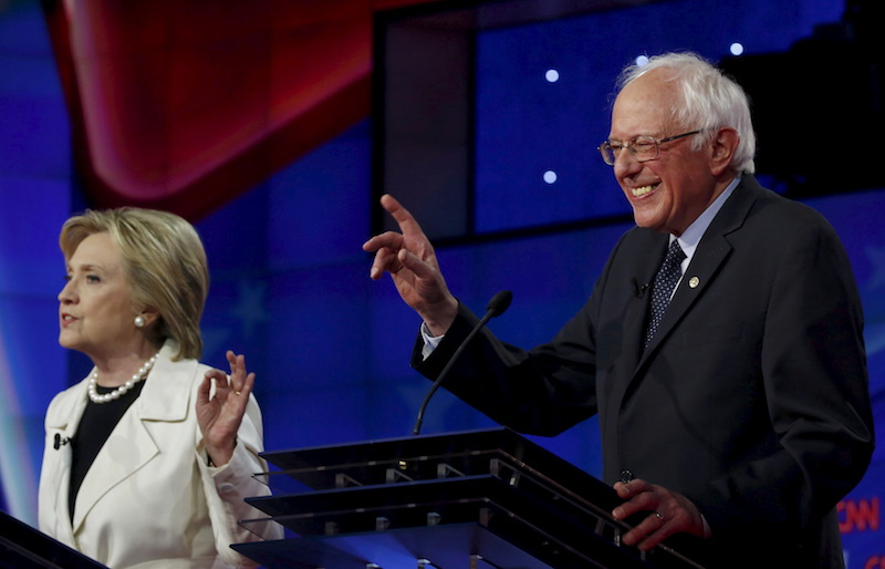 Democratic U.S. presidential candidates Hillary Clinton (L) and Senator Bernie Sanders speak simultaneously during a Democratic debate hosted by CNN and New York One at the Brooklyn Navy Yard in New York April 14, 2016. REUTERS/Lucas Jackson TPX IMAGES OF THE DAY - RTX2A1G8