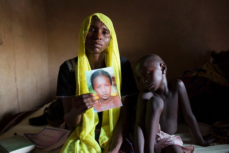 Rachel Daniel, 35, holds up a picture of her abducted daughter Rose Daniel, 17, as her son Bukar, 7, sits beside her at her home in Maiduguri on May 21, 2014. Rose was abducted along with more than 200 of her classmates on April 14 by Boko Haram militants from a secondary school in Chibok, Borno state. Photo courtesy of REUTERS/Joe Penney *Editors: This photo may only be republished with RNS-CHIBOK-GIRLS, originally transmitted on April 12, 2016.