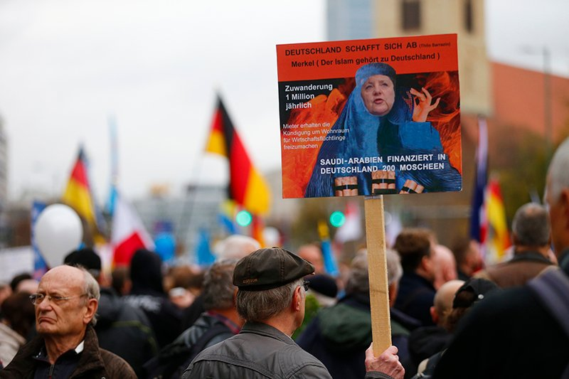 Supporters of the right-wing Alternative for Germany (AfD) demonstrate against the German government's new policy for migrants in Berlin, Germany, on November 7, 2015. The texts read 'Germany abolishes itself' and 'Merkel (Islam belongs to Germany).' Photo courtesy of REUTERS/Hannibal Hanschke *Editors: This photo may only be republished with RNS-GERMAN-CLERIC, originally transmitted on April 28, 2016.